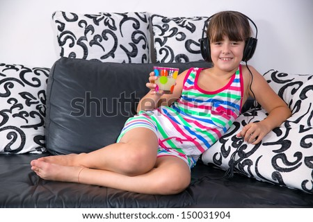 Pretty girl listening to music with headphones and holding a glass of juice - stock photo