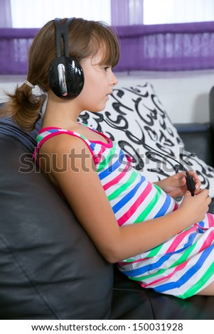 Pretty girl listening to music with headphones  in the living room - stock photo
