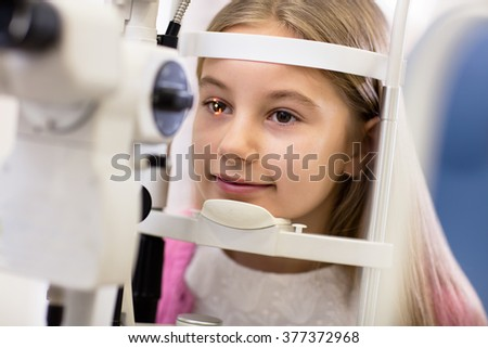Pretty girl look at ophthalmoscope in eye clinic  - stock photo