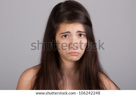Pretty girl looking angry over a grey background - stock photo