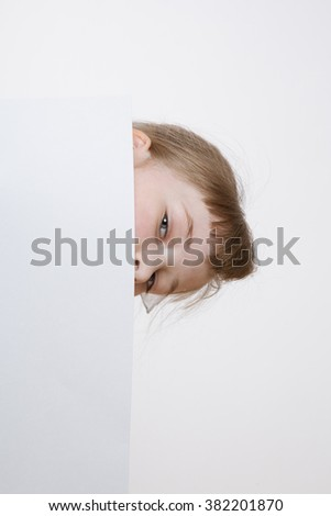 Pretty girl looking out for a big sheet of paper, closeup shot - stock photo