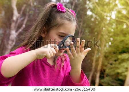 Pretty girl looking through a magnifying glass in the park - stock photo