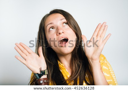 Pretty girl looks up frightened, isolated on a gray background - stock photo
