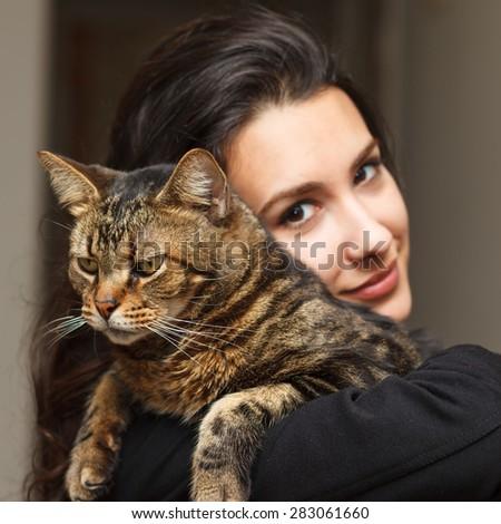 Pretty girl loving her pet tabby cat. - stock photo
