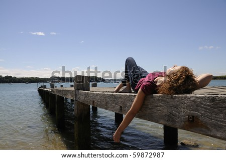 Pretty girl lying and relaxing on landing stage in Brittany, France on a sunny day.