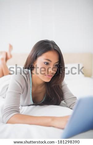 Pretty girl lying on bed using her tablet in her bedroom at home
