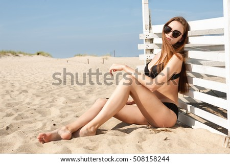 Pretty girl on beach. Picture of happy woman with wind surf on the beach.