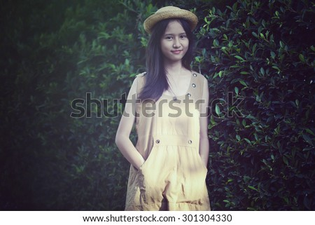 Pretty girl on green leaves background. Portrait woman in Vintage style - stock photo
