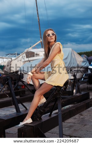 Pretty girl on sea and yacht background. Outdoor lifestyle portrait of woman