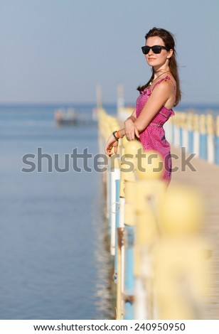Pretty girl on vacation i standing at a pier enjoying sunshine. Woman in sunglasses is waiting for someone at the sea peer. Freedom and waiting concept - stock photo