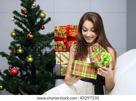 Pretty girl opening gift near the Christmas tree