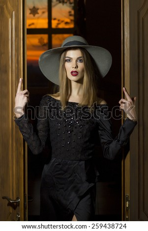 Pretty girl or woman in the hat and black formal dress entering throught the doors - stock photo