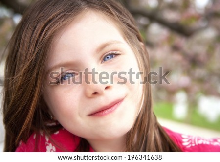 Pretty girl outdoor portrait with cherry blossoms in the background - stock photo