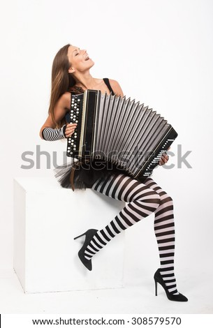 Pretty girl playing the Russian bayan (button accordion) and singing - stock photo