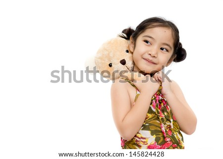 Pretty girl playing with bear doll on white background - stock photo