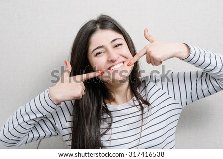 Pretty girl pointing finger on her teeth - stock photo