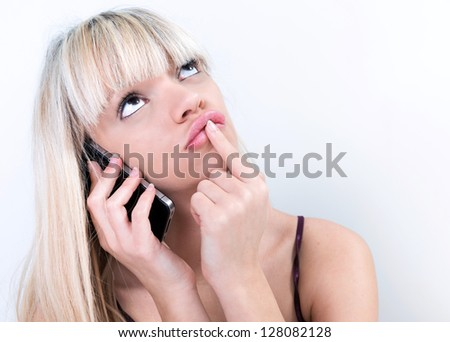 pretty girl pondering while phoning - stock photo