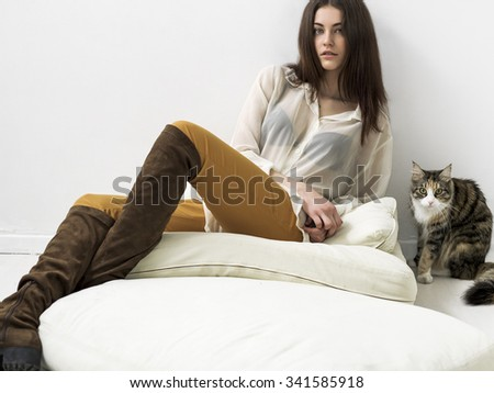 Pretty girl portrait sitting on cushions and looking and cat - stock photo