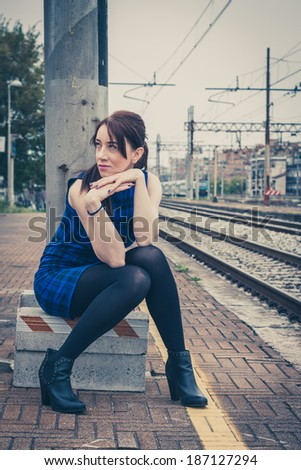 Pretty girl posing along the tracks in a railroad station