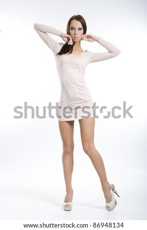 Pretty girl posing in a nice beige dress - stock photo