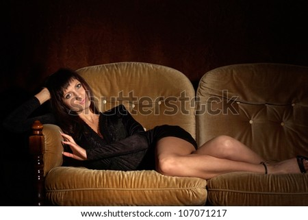 Pretty girl relaxing on a sofa on a black background