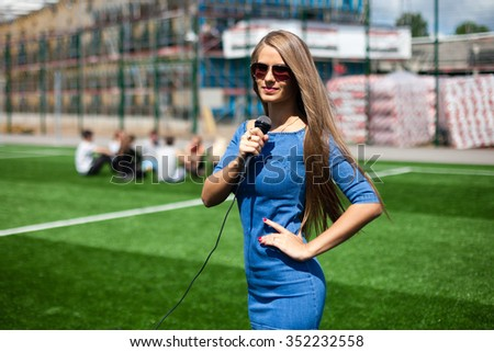 Pretty girl-reporter with microphone on a stadium. - stock photo