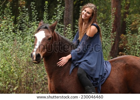 Pretty girl riding a horse without any equipment in nature