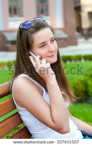 Pretty girl says on his cell sitting on a bench.