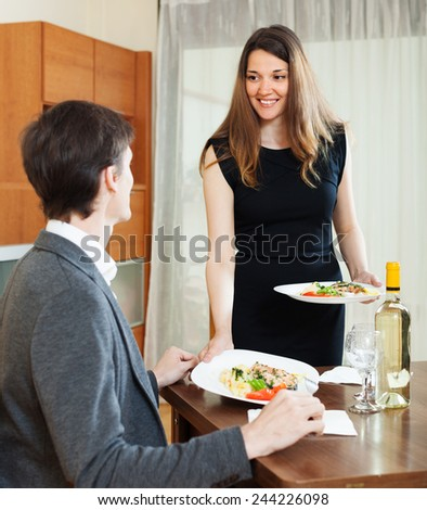 Pretty girl serving dinner to beloved man at table - stock photo