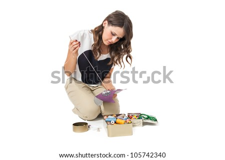 pretty girl sewing fabric on white background - stock photo