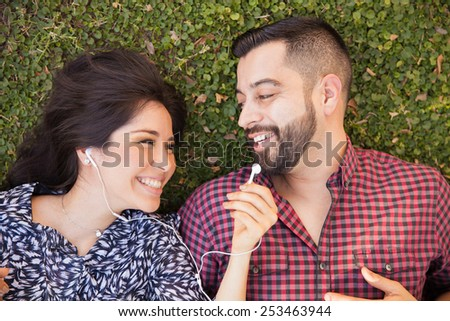 Pretty girl sharing her earbuds with her boyfriend while relaxing at a park - stock photo