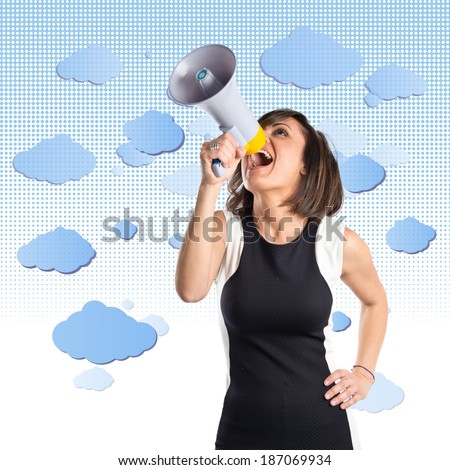 Pretty girl shouting with a megaphone over sky background
