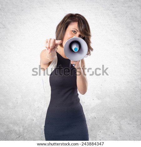 Pretty girl shouting with a megaphone over textured background