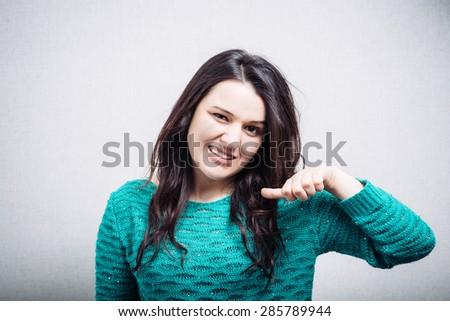 Pretty girl shows thumb - stock photo