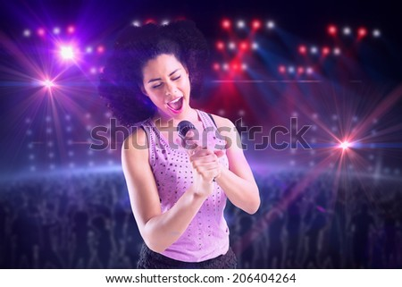 Pretty girl singing against digitally generated nightclub under lights - stock photo
