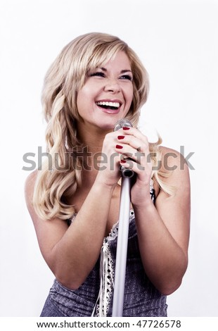Pretty girl singing into microphone.  Young female singer with blond hair singing a song. Woman laying down some vocal tracks. Leader of pop music band on white background.