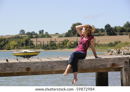 Pretty girl sitting and relaxing on landing stage in Brittany, France on a sunny day. - stock photo