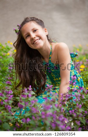 Pretty girl sitting in the grass and flowers - stock photo