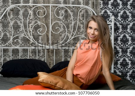 Pretty girl sitting on bed - stock photo