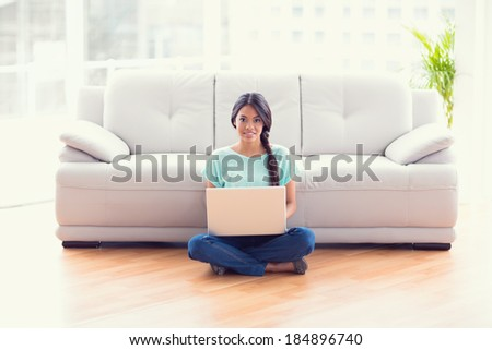 Pretty girl sitting on floor using laptop smiling at camera at home in the living room - stock photo