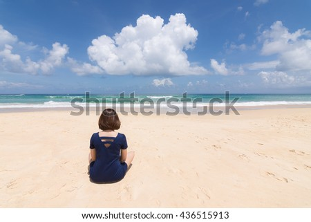 Pretty girl sitting on the beach at Karon Phuket Thailand.