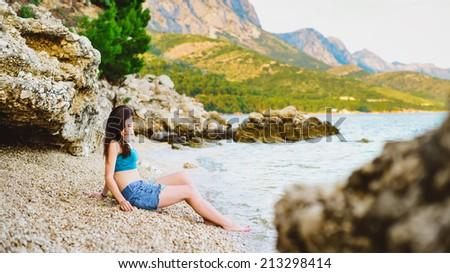 pretty girl sitting on the beach in Croatia - stock photo