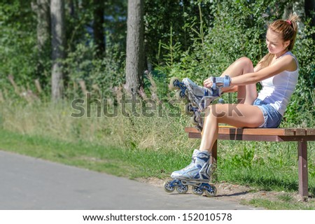 Pretty girl sitting on the bench and putting on inline skates. - stock photo