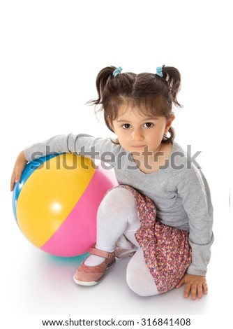 Pretty girl sitting on the floor to play with a large inflatable striped ball-Isolated on white background - stock photo