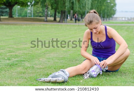 Pretty girl sitting on the grass and putting on inline skates. - stock photo