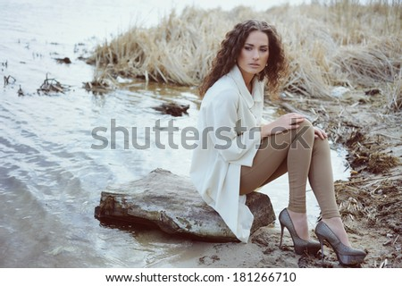 Pretty girl sitting on the shore of the lake - stock photo