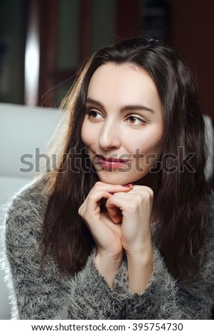 pretty girl sitting with hands near her chin and attentively listening to - stock photo