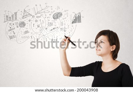 Pretty girl sketching graphs and diagrams on white wall - stock photo