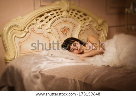 Pretty girl sleeping on the bed in an elegant bedroom - stock photo