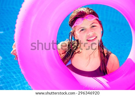 pretty girl smiling in a swimming pool wearing swimming goggles